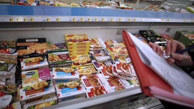Un agent la Direction départementale de la protection de la population (DDPP) contrôle le retrait des produits contenant du cheval, dans un supermarché d'Hérouville Saint-Clair (Calvados), le 26 février 2013. (CHARLY TRIBALLEAU / AFP)