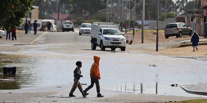 Des enfants passent devant une flaque d'eau après de fortes pluies au Cap, le 26 avril 2018. (REUTERS/Sumaya Hisham)