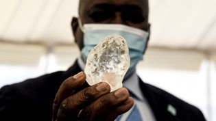 Le président botswanais Mokgweetsi Masisiexhibe fièrement le diamant brut de 1098 carats à Gaborone, la capitale du Botswana, le 16 juin 2021. (MONIRUL BHUIYAN / AFP)