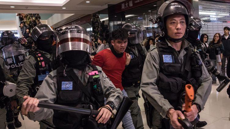 La police retient un homme dans un centre commercial deSheung Shui à Hong Kong, le 28 décembre 2019. (DALE DE LA REY / AFP)