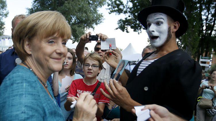 La chancelière allemande, Angela Merkel, signe des autographes pendant une journée portes ouvertes du gouvernement, à Berlin (Allemagne), le 25 août 2013. (FABRIZIO BENSCH / REUTERS)