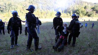 Des gendarmes emmènent un opposant au projet de barrage de Sivens, le 1er septembre 2014, au premier jour des travaux, à Lisle-sur-Tarn (Tarn). (MAXPPP)