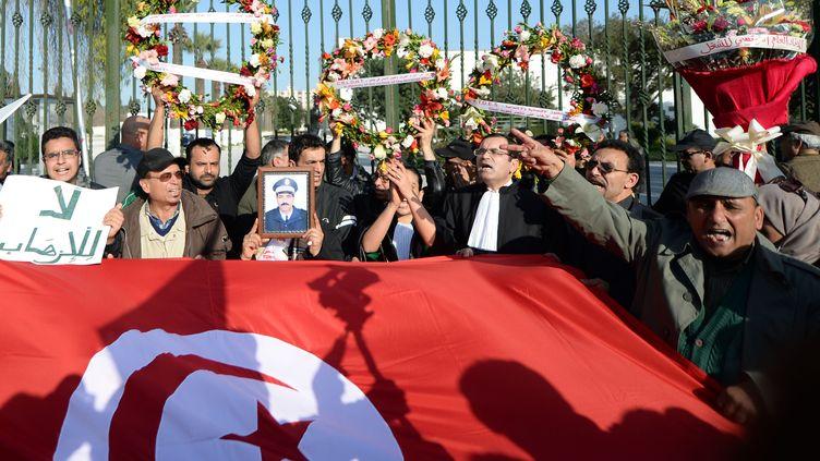 Des manifestants tunisiens devant le musée du Bardo, à Tunis, le 19 mars 2015, au lendemain de l'attaque revendiquée par l'Etat islamique. (FADEL SENNA / AFP)