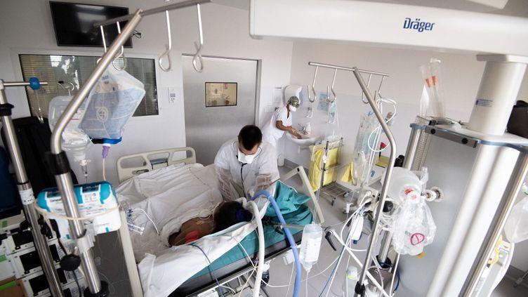 Dessoignants du CHU de Fort-de-France (Martinique) s'occupent d'une patiente atteinte du Covid-19 placée sous assistance respiratoire, le 29 août 2021.   (ALAIN JOCARD / AFP)