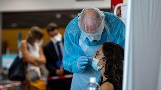 Un infirmier réalise un test de dépistage du Covid-19 le 11 août 2020 à l'aéroport de Lyon-Saint Exupéry sur des voyageurs en provenance de Turquie. (NICOLAS LIPONNE / HANS LUCAS / AFP)