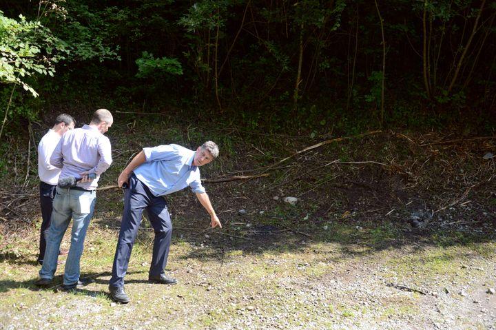 Un homme indique, vendredi 7 septembre 2012, le lieu où les quatre victimesde la tuerie de Chevaline (Haute-Savoie) ont été découvertes. (PHILIPPE DESMAZES / AFP)