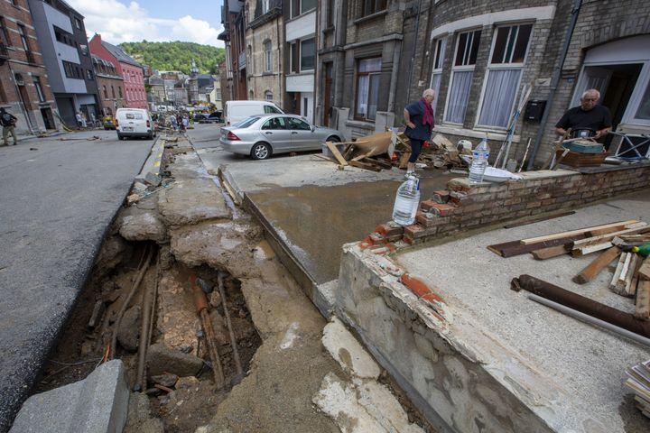 Des résidents de Dinant, en Belgique, constatent les dégâts devant leur domicile, où une rue a été détruite par les inondations, le 25 juillet 2021. (NICOLAS MAETERLINCK / BELGA / AFP)