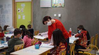 Une enseignante avec un masque de protection dans une classe de CE2 àBruyères-le-Châtel(Essonne), le 19 janvier 2021. (MYRIAM TIRLER / HANS LUCAS / AFP)