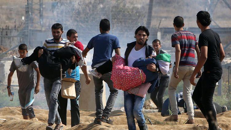 Des femmes palestiniennes sont évacués par des hommes après des tirs de gaz lacrymogène à la frontière entre Israël et la bande de Gaza, le 10 octobre 2015. (MAHMUD HAMS / AFP)