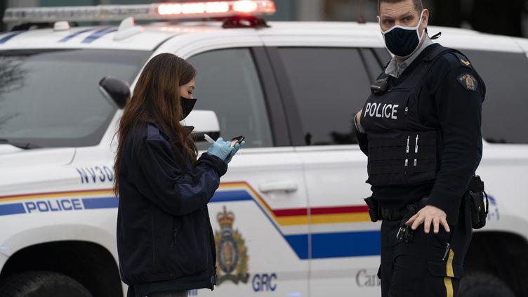 Des policiers aux abords de la bibliothèque de Lynn Valley, dans le nord de Vancouver, au Canada, où une attaque au couteau a eu lieu samedi 27 mars 2021. (JONATHAN HAYWARD / THE CANADIAN PRESS / AP)