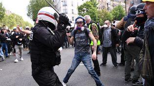 Un policier brandit sa matraque devant un manifestant à Paris, le 1er mai 2019. (ANNE-CHRISTINE POUJOULAT / AFP)