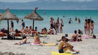 Desvacanciers se baignent sur une plage de Majorque (Espagne), le 15 juin 2017. (JENS KALAENE / ZB / AFP)