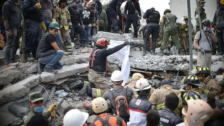 Des secouristes cherchant des survivants dans les décombres d'un des bâtiments qui se sont effondrés à Mexico, après le séisme qui a frappé le Mexique, le 20 septembre 2017. (YURI CORTEZ / AFP)