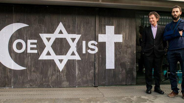 """Combo et Jack Lang devant le message """"Coexist"""" inscrit par le street artist à l'IMA (Institut du Monde Arabe).  (Denis Prezat / Citizenside / AFP)"""