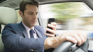 Parmi les conducteurs qui utilisent leur téléphone au volant, un sur cinq reconnaît même consulter ou envoyer des SMS. (FREDERIC CIROU / ALTOPRESS / AFP)