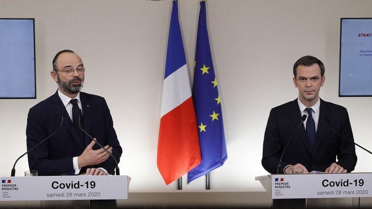 Edouard Philippe, alors Premier ministre, et Olivier Véran, le ministre de la Santé, lors d'une conférence de presse à Paris, le 28 mars 2020. (GEOFFROY VAN DER HASSELT / AFP)