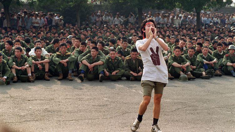 Un étudiant chinois demandent au militaire de rentrer chez eux, le 3 juin 1989, place Tiananmen. (CATHERINE HENRIETTE / FILES)