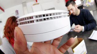 Un chauffagiste explique la nécessité et l'obligation de poser un détecteur de fumée dans les habitations pour la sécurité des occupants le 8 février 2015. (MAXPPP)