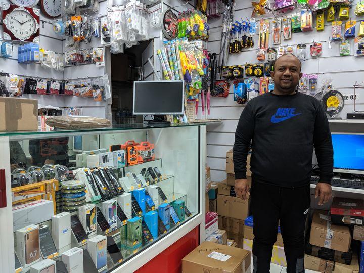 Ataur Rahman pose devant des colis, dans sa boutique d'informatique située dans le 15e arrondissement de Paris, le 18 décembre 2019. (CHARLOTTE CAUSIT / FRANCEINFO)