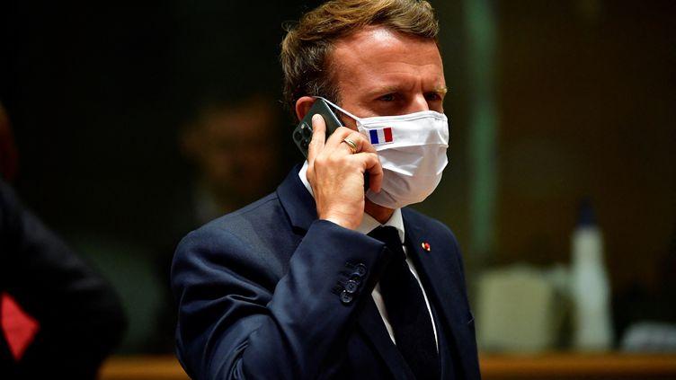 Le président de la République, Emmanuel Macron, téléphone durant un sommet de l'Union européenne à Bruxelles (Belgique), le 20 juillet 2020. (JOHN THYS / POOL / AFP)