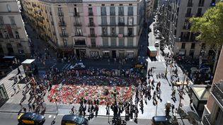 Vue aérienne des fleurs et des bougies disposées, le 22 août 2017, sur une place de Barcelone en mémoire des victimes des attentats qui ont fait 15 morts en Catalogne. (LLUIS GENE / AFP)