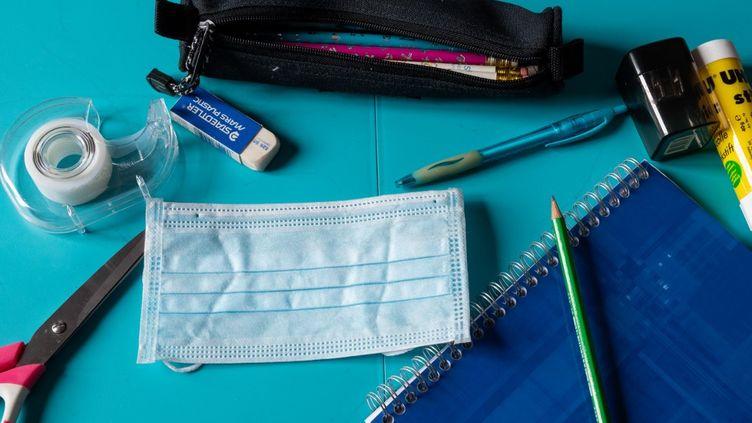 Un masque antiprojection au milieu de fournitures scolaires. (RICCARDO MILANI / HANS LUCAS / AFP)