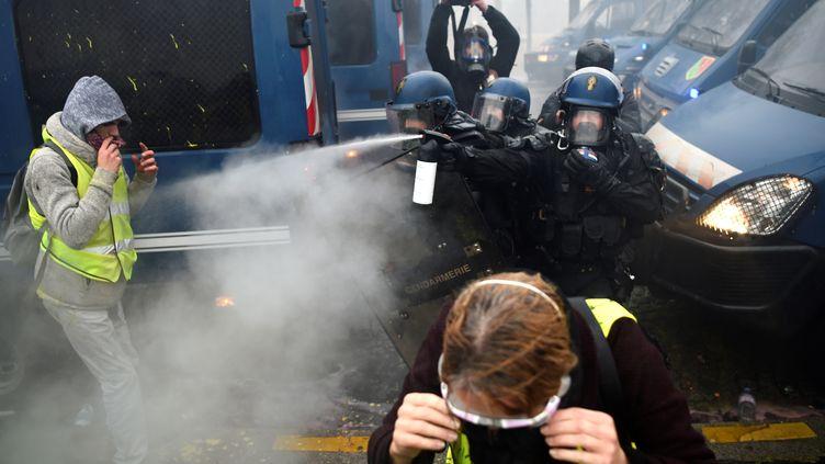 Des policiers aspergent de gaz lacrymogène des manifestants, le 1er décembre 2018, à Paris. (LUCAS BARIOULET / AFP)