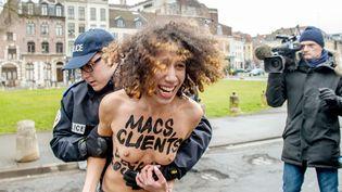 Un policier arrête une Femen qui vient de se jeter sur la voiture de DSK, peu avant l'audience du 10 février 2015 dans le procès du Carlton, à Lille (Nord). (PHILIPPE HUGUEN / AFP)