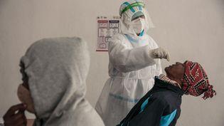 Un travailleur de la santé prend un écouvillon nasal pour tester un patient au Centre médical Covid-19 d'Andohatapenaka, à Antananarivo, le 20 juillet 2020. (RIJASOLO / AFP)