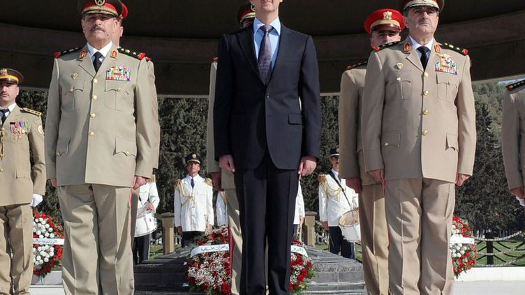 Bachar al-Assad avec son ministre de la Défense (à dr.) et son chef détat-major (à g.), le 6 octobre 2011 à Damas (Syrie). (SANA / AFP)