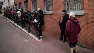 Une file d'attente devant un centre de vaccination, le 15 janvier 2021, à Paris. (MARTIN BUREAU / AFP)