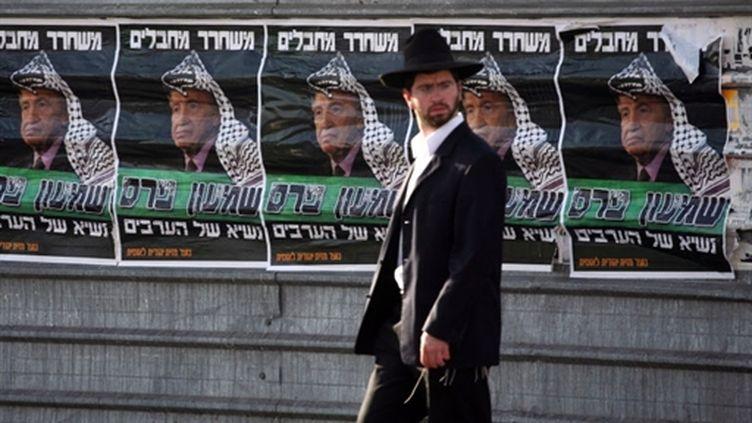 Un juif orthodoxe devant des affiches représentant Shimon Peres coiffé d'un keffieh pour le dénoncer comme pro-arabe (AFP/MENAHEM KAHANA)