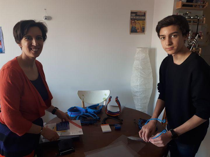 Roméo et sa mère, Julie, en train d'assembler des masques. (SOPHIE DELPONT / RADIOFRANCE)
