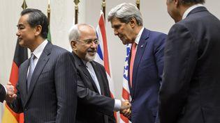 Le ministre des Affaires étrangères iranien, Mohamad Javad Zarif, serrant la main de son homologue américain John Kerry, le 24 novembre 2013 à Genève (Suisse). (FABRICE COFFRINI / AFP)