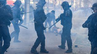 Des policiers arrêtent un manifestant samedi 16 mars sur les Champs-Elysées, à Paris. (ALAIN JOCARD / AFP)