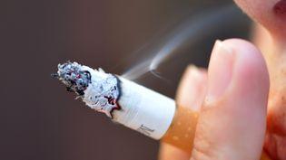 Une femme fume une cigarette. (image d'illustration) (ERIC FEFERBERG / AFP)