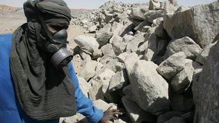 Un employé de la mine d'uranium à ciel ouvert de Arlit dans le désert nigérien, inspecte des roches contenant de l'uranium qui sert de combustible nucléaire. (Photo AFP/Pierre Verdy)