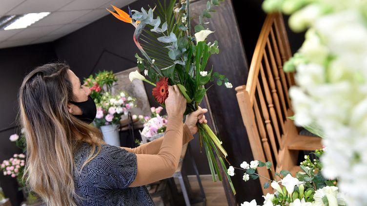 Une fleuriste en train de composer un bouquet (illustration). (R?MY PERRIN / MAXPPP)
