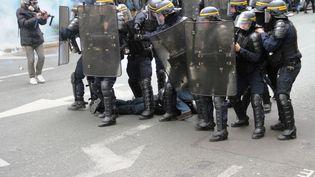 Des CRS autour d'un officier blessé, à Paris, le 28avril 2016 pendant la manifestation contre la loi Travail. (MOURAD LAFFITTE / AFP)
