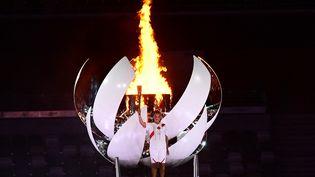 La joueuse de tennis Naomi Osaka, après avoir allumé la flamme olympique,à la cérémonie d'ouverture des Jeux olympiques,à Tokyo (Japon), le 23 juillet 2021. (FRANCK FIFE / AFP)