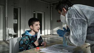 Un écolier réalise un test salivaire, à Eysines (Gironde), le 25 février 2021. (PHILIPPE LOPEZ / AFP)