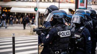 """Un groupe de policiers, dont l'unpointe un lanceur de balles de défense (LBD) en direction de manifestants, à la Gare de Lyon (Paris), lors d'une manifestationdes """"gilets jaunes'', le 16 novembre 2019. (XOSE BOUZAS / HANS LUCAS / AFP)"""