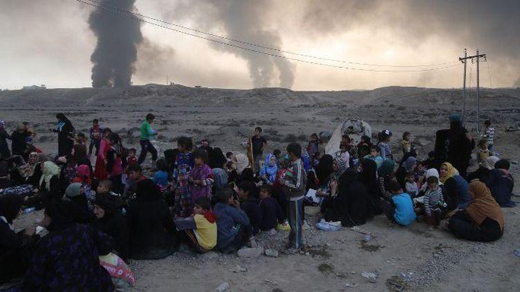 Des réfugiés irakiens fuyant les quartiers de Mossoul sous contrôle de Daech, à leur arrivée dans la ville de Qayyarah, le 18 octobre 2016. (Hemn Baban/ANADOLU AGENCY/AFP)