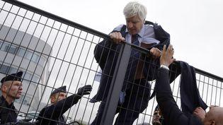 Le directeur des activités long courrier d'Air France escalade une grille de sécurité pour échapper à ses agresseurs, le 5 octobre 2015 au siège d'Air France, à Roissy (Val-d'Oise). (KENZO TRIBOUILLARD / AFP)
