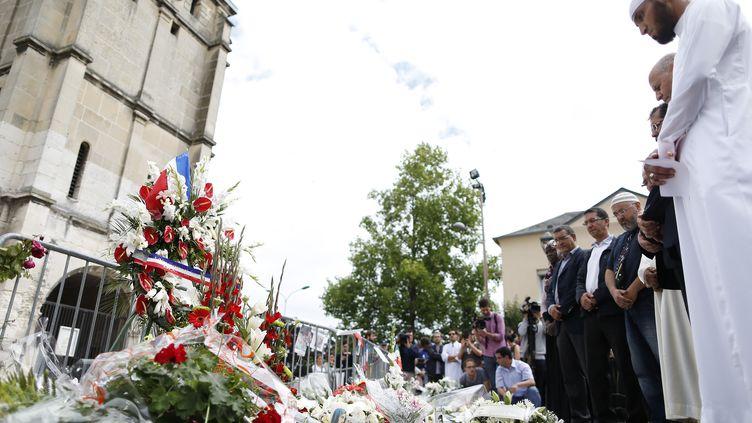 Des imams posent des fleurs devant l'église de Saint-Etienne-du-Rouvray (Seine-Maritime), le 29 juillet 2016, en hommage au prêtre tué par des jihadistes. (CHARLY TRIBALLEAU / AFP)