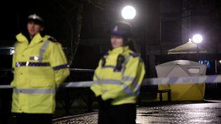 La police britannique monte la garde, le 5 mars 2018, devant un banc à Salisbury (Royaume-Uni) où deux personnes, dont un ancien espion russe, ont été retrouvées inconscientes la veille. (TOBY MELVILLE / REUTERS)