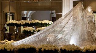 A l'entrée de la galerie de l'Hôtel du Four Seasons, la robe de mariée et son voile, en tulle rebrodé de paillettes, pierres et cristaux est entourée de 9.000 roses blanches «Avalanche».  (DR)