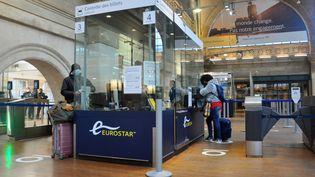 Des passagers patientent devant un guichet de la gare du Nord, le 21 décembre 2020 à Paris. (FLORENCE GALLEZ / SPUTNIK / AFP)