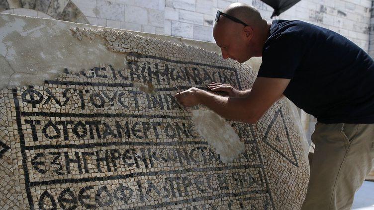 Un archéologue continue à nettoyer la mosaïque découverte à Jérusalem.  (AHMAD GHARABLI / AFP)