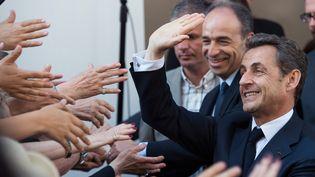Nicolas Sarkozy (D) et Jean-François Copé derrière lui, le 8 juillet 2013, devant le siège de l'UMP à Paris. (MARTIN BUREAU / AFP)